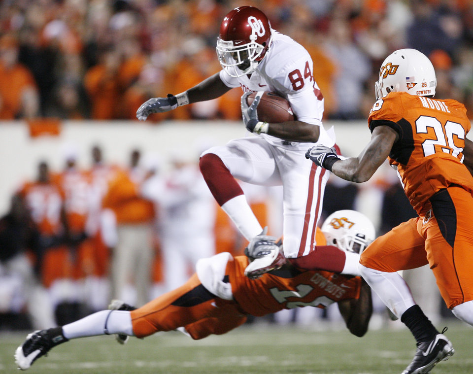 OU's Quentin Chaney jumps over OSU's Perrish Cox as Quitnon Moore closes in during the first half of the college football game between the University of Oklahoma Sooners (OU) and Oklahoma State University Cowboys (OSU) at Boone Pickens Stadium on Saturday, Nov. 29, 2008, in Stillwater, Okla. STAFF PHOTO BY BRYAN TERRY