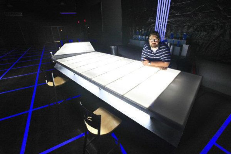 Photo - Jason Robison, host team pastor at the LifeChurch.tv northwest campus in Warr Acres, stands behind a futuristic refreshment bar in the church's lobby. The bar area was created to look one seen in the film