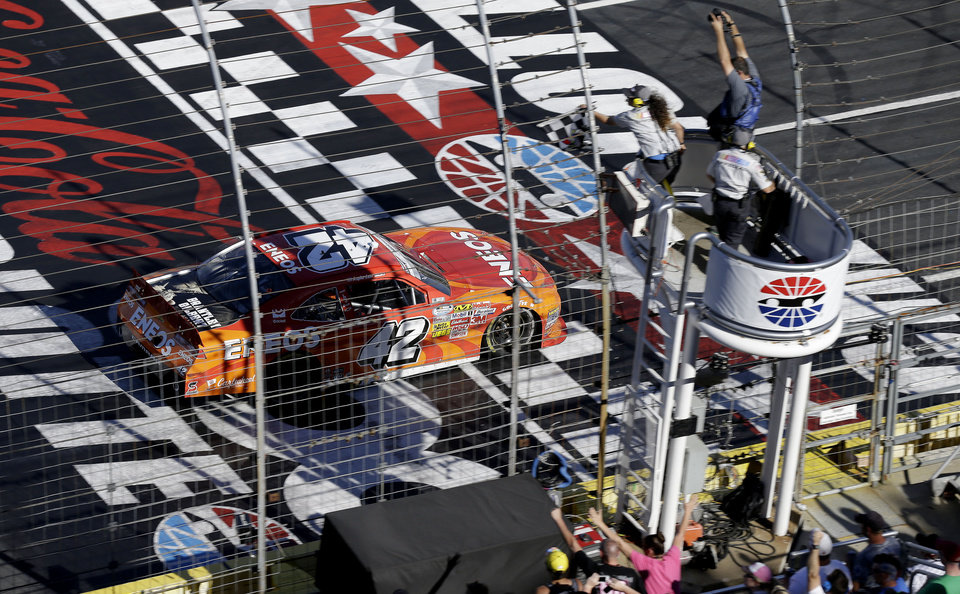 Photo - Kyle Larson (42) takes the checkered flag to win the NASCAR Nationwide series History 300 auto race at the Charlotte Motor Speedway in Concord, N.C., Saturday, May 24, 2014. (AP Photo/Gerry Broome)