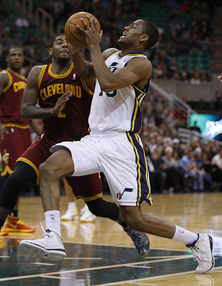 Photo - Utah Jazz's Alec Burks, right, drives past Cleveland Cavalier's Kyrie Irving during the second half of an NBA basketball game in Salt Lake City, Friday, Jan. 10, 2014. Cavaliers defeated the Jazz 113-102. (AP photo/George Frey)