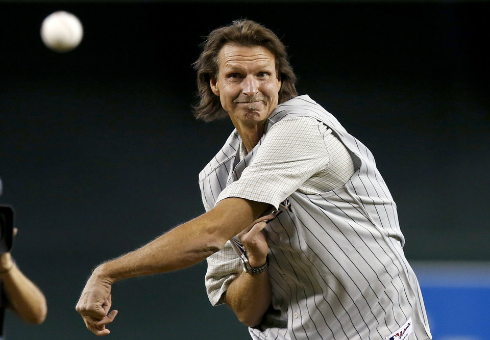 Photo - Former Arizona Diamondbacks pitcher Randy Johnson throws out the first pitch during ceremonies commemorating the 10th anniversary of Johnson's perfect game prior to a baseball game between the Diamondbacks and the Los Angeles Dodgers on Sunday, May 18, 2014, in Phoenix. (AP Photo/Ross D. Franklin)