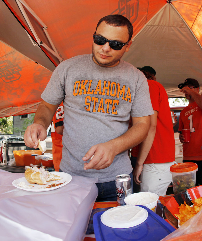 Photo - OSU fan Jeremy Janowiak of Oklahoma City gets some dip for his plate while tailgating before the Cowboys game vs. UL-Lafayette. Photo by Nate Billings, The Oklahoman