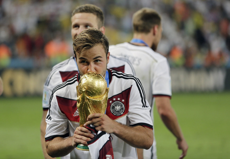 Photo - Germany's Mario Goetze kisses the trophy after the World Cup final soccer match between Germany and Argentina at the Maracana Stadium in Rio de Janeiro, Brazil, Sunday, July 13, 2014. Germany won the match 1-0. (AP Photo/Matthias Schrader)