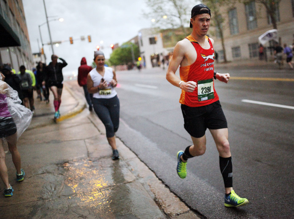 Photo - Marathon runner James Strahorn runs for cover in a parking garage to escape the pouring rain before the start the 14th Annual Oklahoma City Memorial Marathon in Oklahoma City, Sunday, April 27, 2014. The marathon was delayed over two hours beyond it's original start time of 6 a.m. Photo by KT King/The Oklahoman