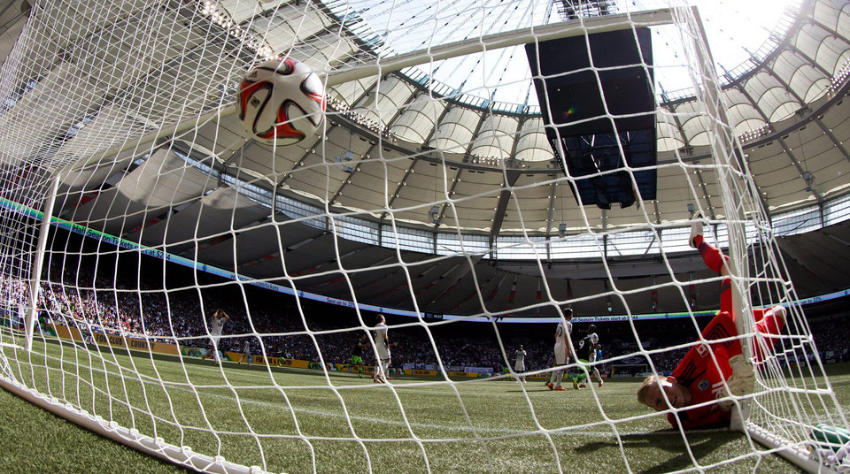 Photo - Vancouver Whitecaps' goalkeeper David Ousted, right, of Denmark, looks at the back of the net after allowing a goal to Seattle Sounders' Chad Barrett during the first half of an MLS soccer game in Vancouver, British Columbia, Saturday, May 24, 2014. (AP Photo/The Canadian Press, Darryl Dyck)