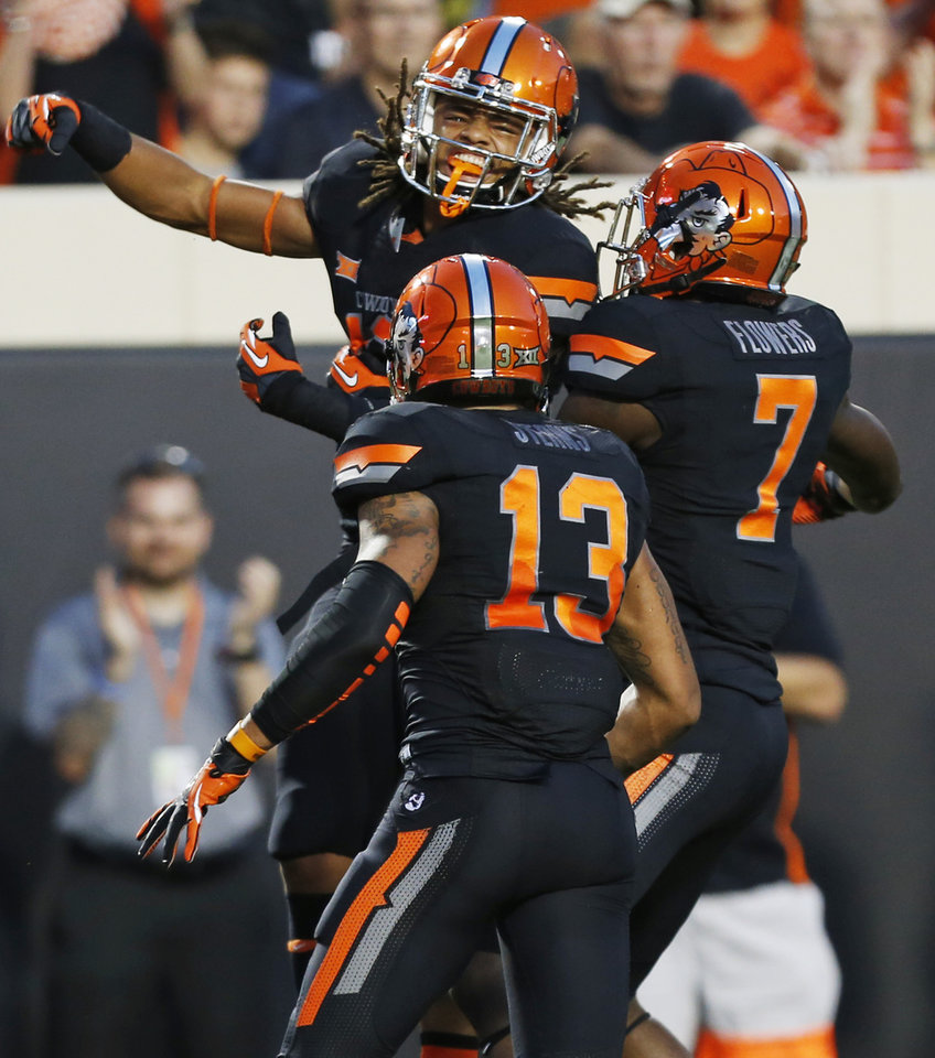 Photo - Oklahoma State's Ramon Richards (18), top, Jordan Sterns (13) and Tre Flowers (7) celebrate an interception by Richards during a college football game between the Oklahoma State Cowboys (OSU) and the Texas Tech Red Raiders at Boone Pickens Stadium in Stillwater, Okla., Thursday, Sept. 25, 2014. Photo by Nate Billings, The Oklahoman