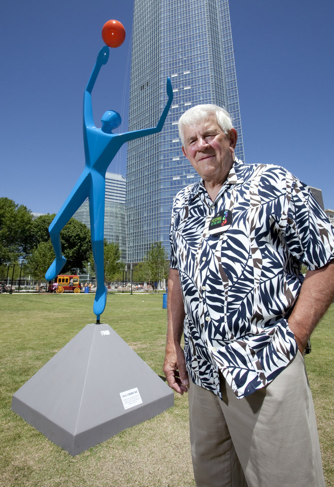 Sculptor Jim Stewart with Stewart Designs stands next to his sculpture