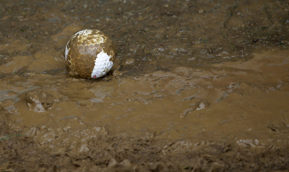Photo - A the golf ball of Graham Delaet, of Canada, sits in the mud on the fourth hole during the third round of the PGA Championship golf tournament at Valhalla Golf Club on Saturday, Aug. 9, 2014, in Louisville, Ky. (AP Photo/David J. Phillip)