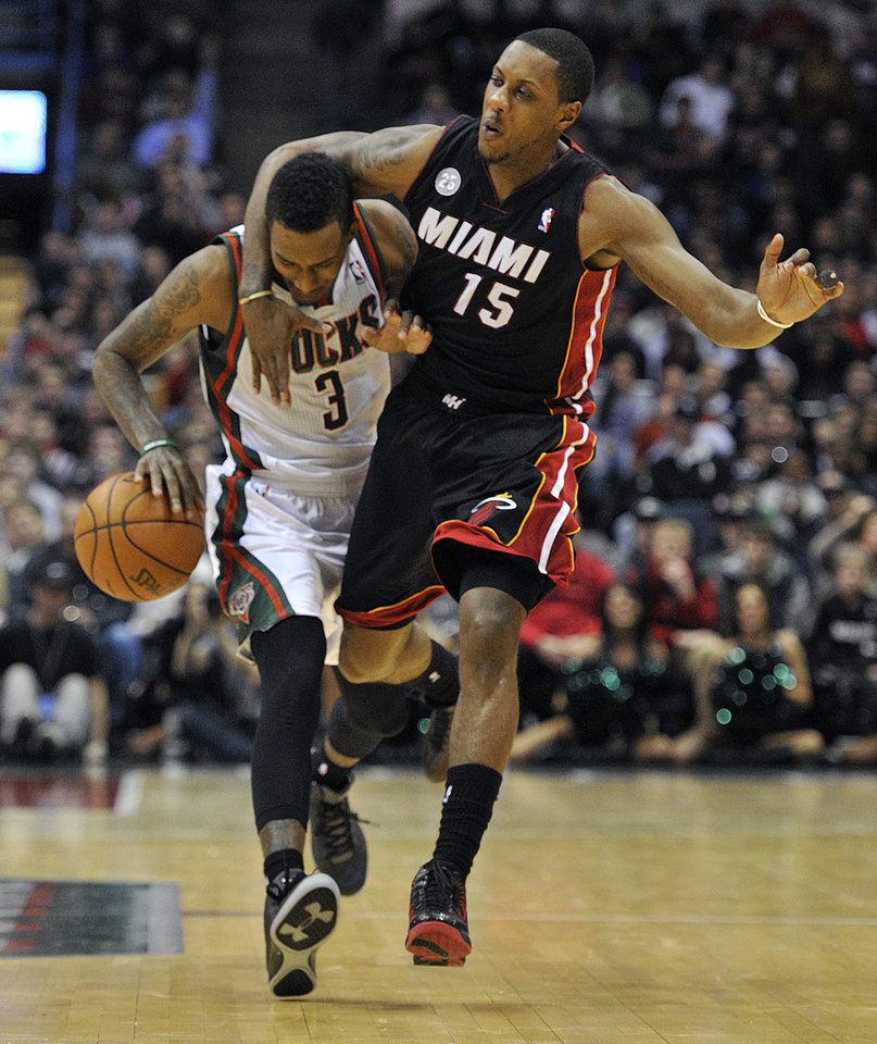 Milwaukee Bucks' Brandon Jennings (3) is fouled by Miami Heat's Mario Chalmers (15) during the second half of an NBA basketball game on Saturday, Dec. 29, 2012, in Milwaukee. The Bucks defeated the Heat 104-85. (AP Photo/Jim Prisching)