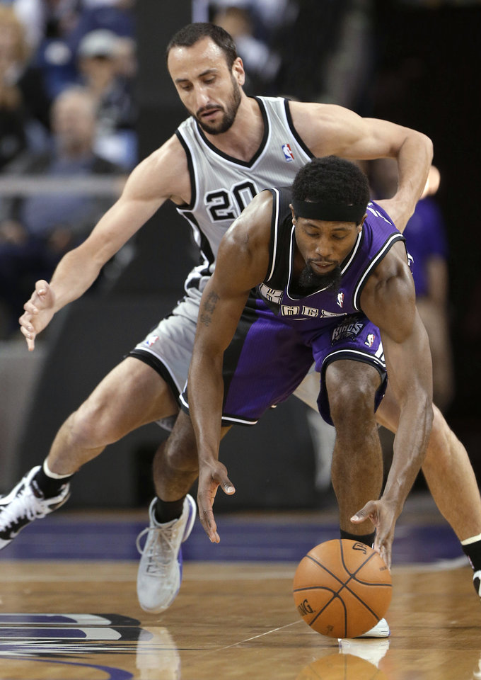 Photo - Sacramento Kings forward John Salmons, right, picks up the ball in front of San Antonio Spurs guard Manu Ginobili, of Argentina, during the first quarter of an NBA basketball game in Sacramento, Calif., Tuesday, Feb. 19, 2013. (AP Photo/Rich Pedroncelli)