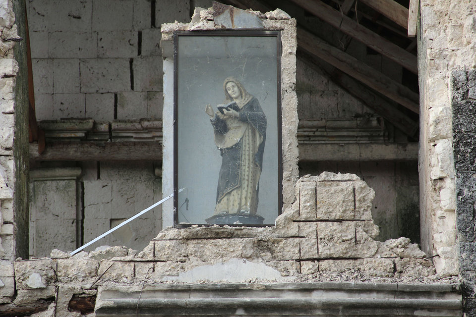 Photo - A religious icon remains encased amid the rubble in Bohol province in central Philippines Wednesday, Oct. 16, 2013, a day after a 7.2-magnitude quake hit Bohol and Cebu provinces. The quake that struck the central Philippines and killed more than a hundred people also dealt a serious blow to the region's historical and religious legacy by heavily damaging a dozen or more churches, some of them hundreds of years old.  (AP Photo/ Kiko Rosario)
