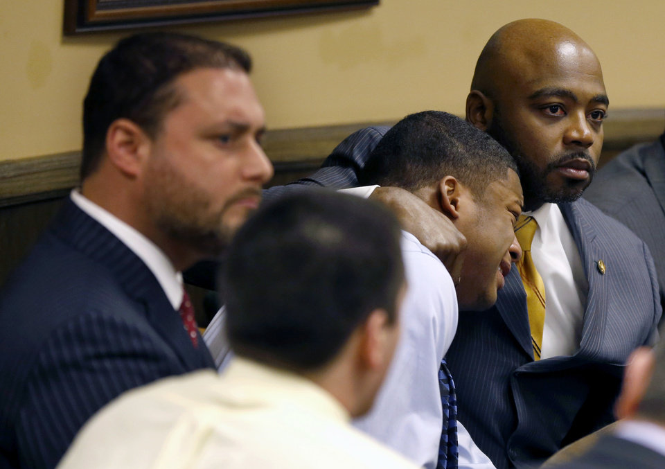 Defense attorney Walter Madison, right, holds his client, 16-year-old Ma\'Lik Richmond, second from right, while defense attorney Adam Nemann, left, sits with his client Trent Mays, foreground, 17, as Judge Thomas Lipps pronounces them both delinquent on rape and other charges after their trial in juvenile court in Steubenville, Ohio, Sunday, March 17, 2013. Mays and Richmond were accused of raping a 16-year-old West Virginia girl in August 2012. (AP Photo/Keith Srakocic, Pool)