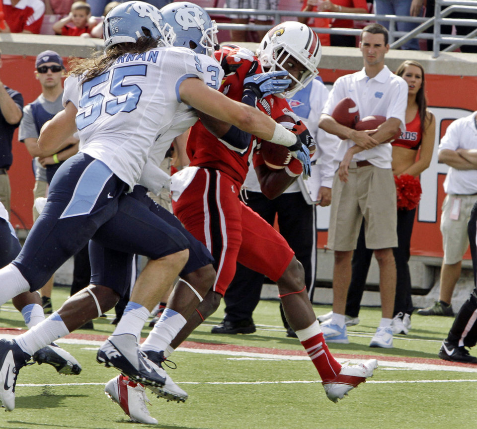 Photo -   Louisville running back Senorise Perry fights to break free of North Carolina defenders Sam Smiley (3) and Tommy Heffeman (55) to get to the end zone to score a touchdown during the first half of an NCAA college football game in Louisville, Ky., Saturday, Sept. 15, 2012. (AP Photo/Garry Jones)