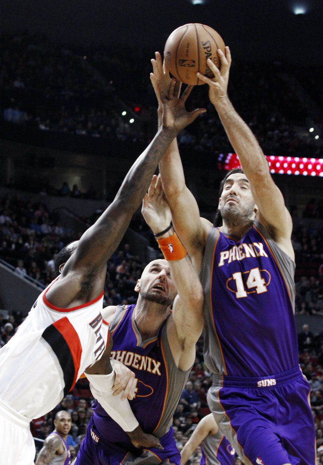 Phoenix Suns forward Luis Scola, right, from Argentina, and center Marcin Gortat, middle, from Poland, battle for a rebound with Portland Trail Blazers center J.J. Hickson during the first quarter of an NBA basketball game in Portland, Ore., Saturday, Dec. 22, 2012.(AP Photo/Don Ryan)