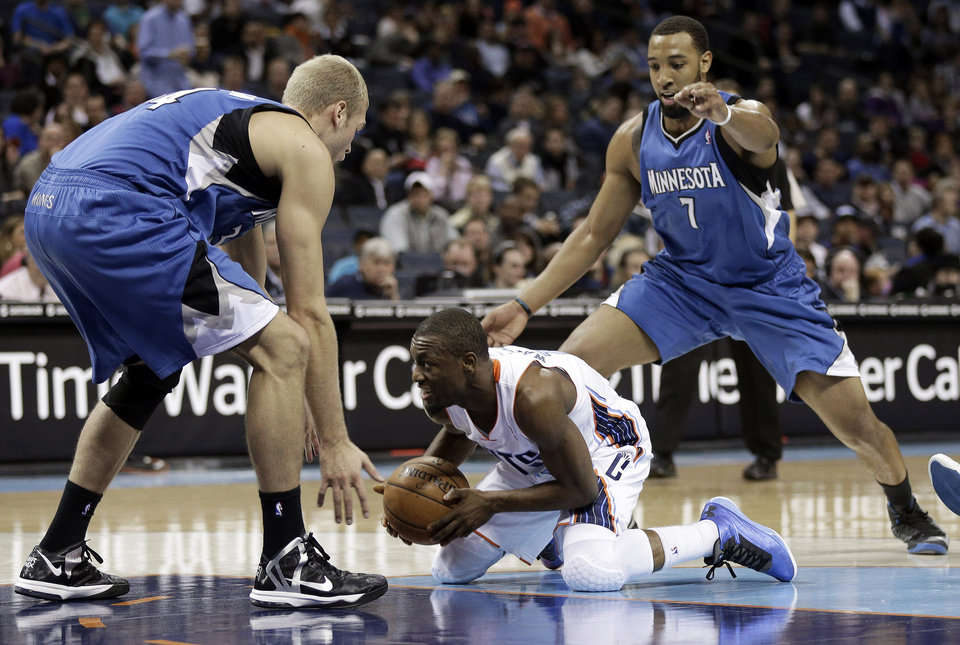 Charlotte Bobcats' Kemba Walker, center, looks to pass as he is trapped by Minnesota Timberwolves' Greg Stiemsma, left, and Derrick Williams, right. during the first half of an NBA basketball game in Charlotte, N.C., Saturday, Jan. 26, 2013. (AP Photo/Chuck Burton)