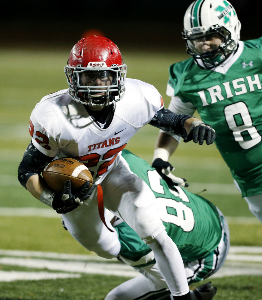 Photo - Titan running back Garrett Asher (22) eludes the tackle of Austin Hopfer (82) and Bobby Sweeney (8) as the Bishop McGuinness Irish play the Carl Albert Titans in a Class 5A semi-final playoff game at Harve Collins Field on Friday, Nov. 23, 2012  in Norman, Okla. Photo by Steve Sisney, The Oklahoman