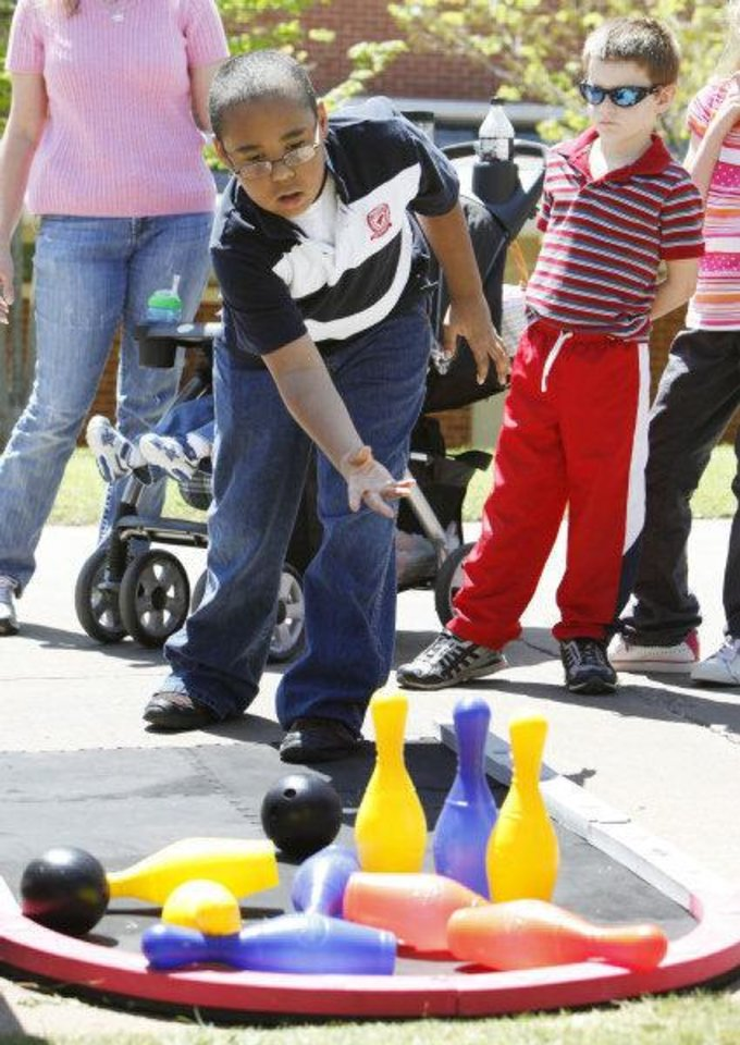 Photo - Aaron Wilson, 9, tries his hand at yard bowling during an Easter egg hunt and carnival Saturday at Plunkett Park at the University of Central Oklahoma in Edmond. Photo by Paul Hellstern, The Oklahoman  PAUL HELLSTERN