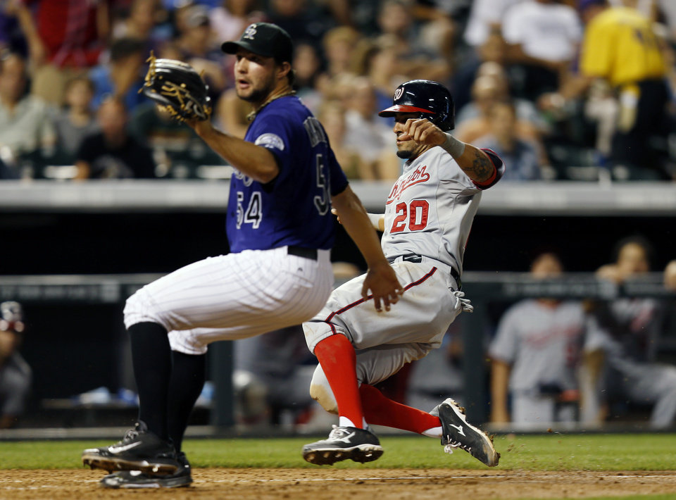 Photo - Washington Nationals' Ian Desmond (20) scores as Colorado Rockies relief pitcher Tommy Kahnle (54)  covers home plate during the seventh inning of a baseball game on Monday, July 21, 2014, in Denver. (AP Photo/Jack Dempsey)