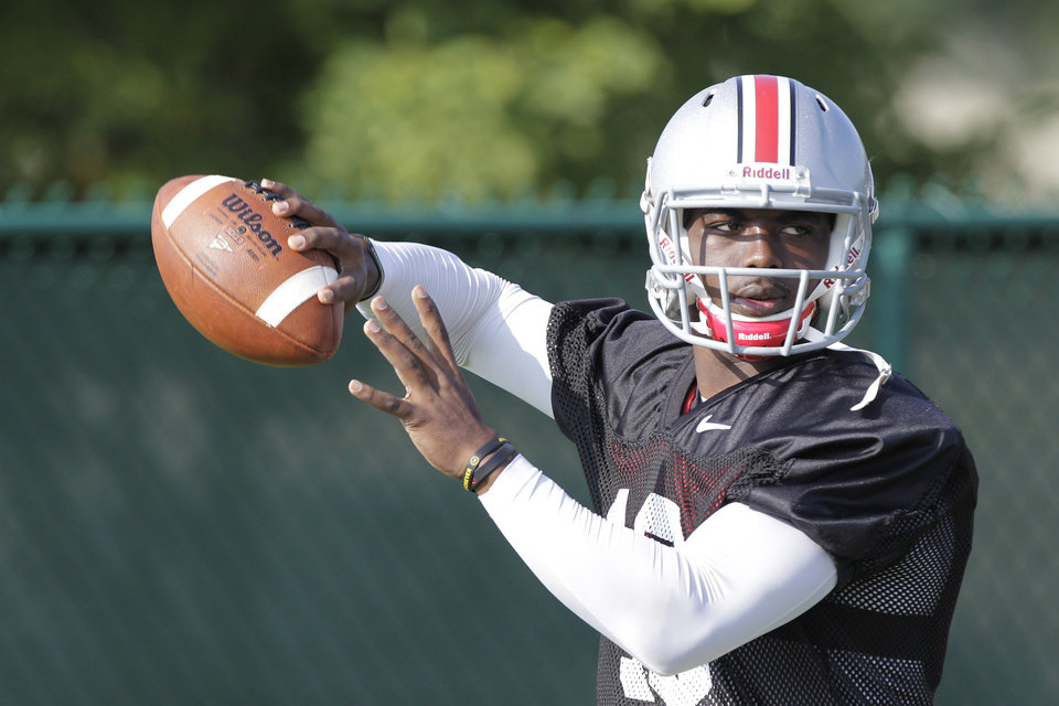 Photo - FILE - This Saturday, Aug. 9, 2014, file photo shows Ohio State quarterback J.T. Barrett throwing a pass during an NCAA college football practice in Columbus, Ohio. Barrett, a redshirt freshman who's never taken a collegiate snap, is set to start when the Buckeyes open their season on Aug. 30 against Navy. Braxton Miller, a two-time Big Ten player of the year, tore the labrum of his (right) throwing shoulder on an unrushed, seven-yard pass on Monday. (AP Photo/Jay LaPrete, File)
