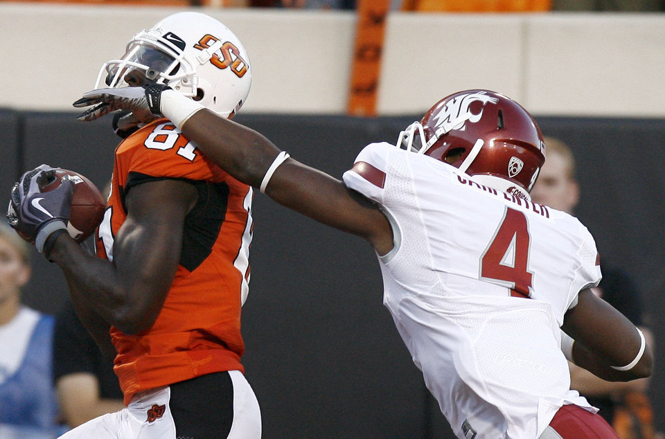 Photo - OSU's Justin Blackmon scores a touchdown as WSU's Anthony Carpenter(4)  tries to bring him down during the college football game between the Washington State Cougars (WSU) and the Oklahoma State Cowboys (OSU) at Boone Pickens Stadium in Stillwater, Okla., Saturday, September 4, 2010. Photo by Sarah Phipps, The Oklahoman