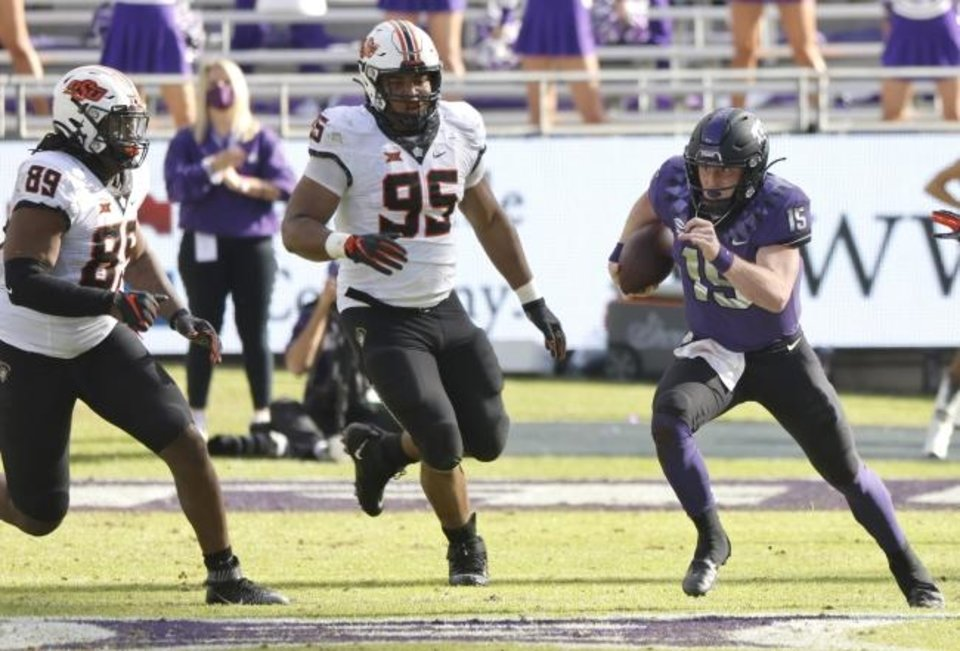Photo -  Oklahoma State's Tyler Lacy (89) and Israel Antwine (95) pursue TCU quarterback Max Duggan (15) during the second half of the Horned Frogs' 29-29 win Saturday in Fort Worth, Texas. [AP Photo/Ron Jenkins]
