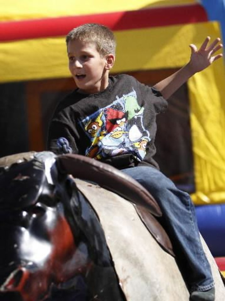 Photo - Patrick Olinger, 10, rides a mechanical bull at a Fourth of July Celebration in Seminole, Okla., July 4, 2012. Photo by Garett Fisbeck, The Oklahoman