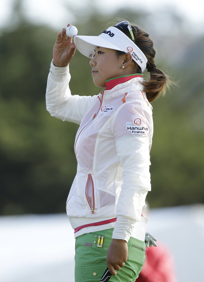 Photo - Jenny Shin holds up her ball on the 18th green of the Lake Merced Golf Club after finishing the third round of the Swinging Skirts LPGA Classic golf tournament on Saturday, April 26, 2014, in Daly City, Calif. (AP Photo/Eric Risberg)