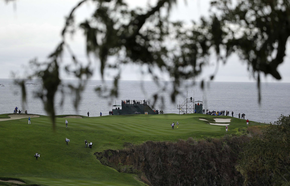 Photo - The playing group of Aaron Baddeley, Kenny G, Lucas Glover and Tom Dreesen make their way up to the sixth green of the Pebble Beach Golf Links during the second round of the AT&T Pebble Beach Pro-Am golf tournament on Friday, Feb. 7, 2014, in Pebble Beach, Calif. (AP Photo/Eric Risberg)