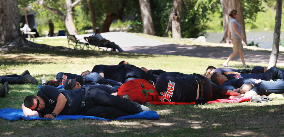 Photo - Firefighters take a sleep break Sunday, June 15, 2014 in Riverside Park in Kernville, Calif., after battling the Shirley Fire all night on the night shift. The wildfire has consumed more than 1800 acres and continues burning with several hundred personnel fighting the fire including hand crews, helicopters, and air tankers from multiple firefighting agencies. (AP photo/The Bakersfield Californian, Casey Christie)  MAGS OUT, TV OUT, NO SALES, MANDATORY CREDIT