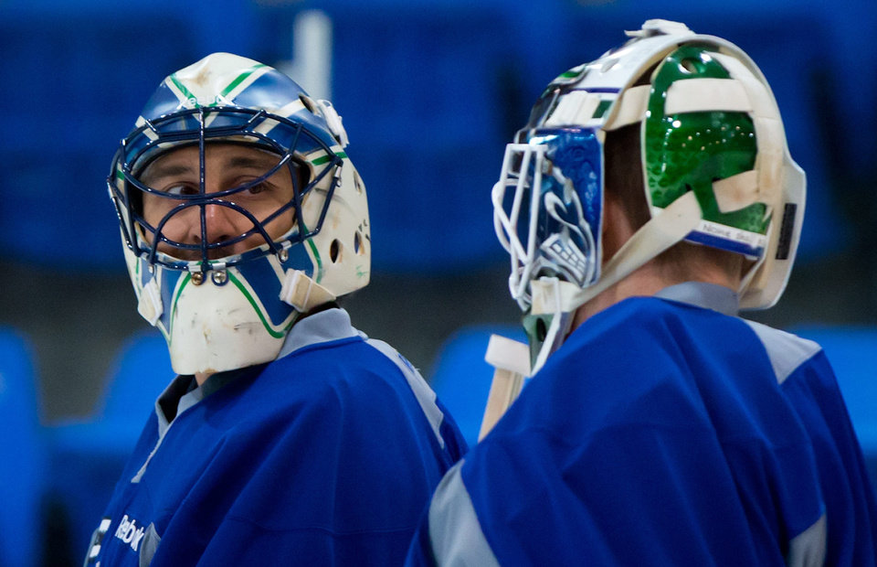 Photo - Vancouver Canucks' goalies Roberto Luongo, left, and Cory Schneider talk during an informal hockey practice at the University of British Columbia in Vancouver, British Columbia on Friday Jan. 11, 2013. (AP Photo/The Canadian Press, Darry; Dyck)