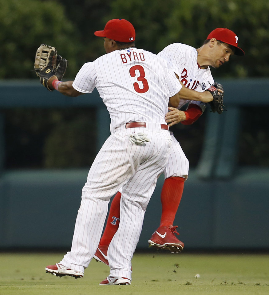 Photo - Philadelphia Phillies right fielder Marlon Byrd (3) collides with center fielder Grady Sizemore after Byrd caught a fly out by Arizona Diamondbacks' Tuffy Gosewisch during the third inning of a baseball game, Saturday, July 26, 2014, in Philadelphia. (AP Photo/Matt Slocum)