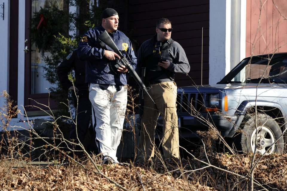Photo - Law enforcement canvass an area following a shooting at the Sandy Hook Elementary School in Newtown, Conn. where authorities say a gunman opened fire, leaving 27 people dead, including 20 children, Friday, Dec. 14, 2012.(AP Photo/Jessica Hill) ORG XMIT: CTJH112