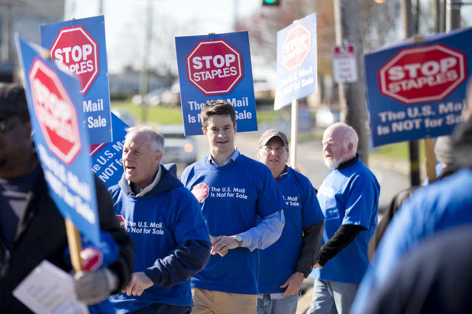 Photo - Democratic Congressional hopeful Kevin Strouse, center, pickets with postal workers and their supporters outside of a U.S. Postal Service facility Thursday, April 24, 2014, in Philadelphia.  Last year, Staples office supply stores began providing postal services under a pilot program that now includes some 80 stores. The American Postal Workers Union objects because the program replaces well-paid union workers with low-wage nonunion workers. (AP Photo/Matt Rourke)