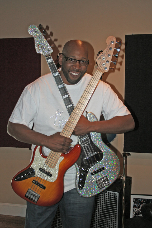 Photo - Musician/former University of Oklahoma (OU) college basketball/NBA basketball player Wayman Tisdale with bass guitars