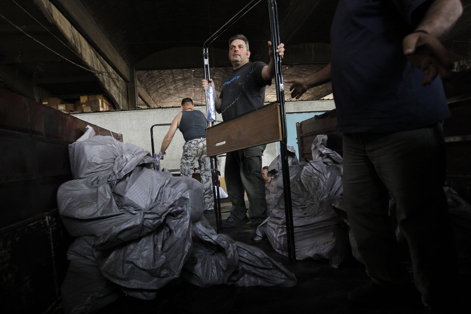Photo -   Workers fill a truck with ballot papers and voting booth in Athens' municipality's warehouse, before delivering them to the polling stations around Athens, on Thursday, May 3, 2012. Greeks head to the polls in early general elections on May 6 .(AP Photo/Petros Giannakouris)
