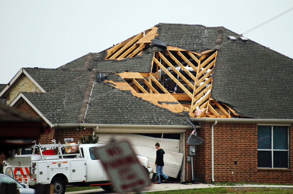 Photo - A man walks in front of a home damaged by Wednesday's tornado in Cleburne, Texas on Thursday, May 16, 2013. Ten tornadoes touched down in several small communities in Texas overnight, leaving at least six people dead, dozens injured and hundreds homeless. Emergency responders were still searching for missing people Thursday afternoon. (AP Photo/Ron Russek II)