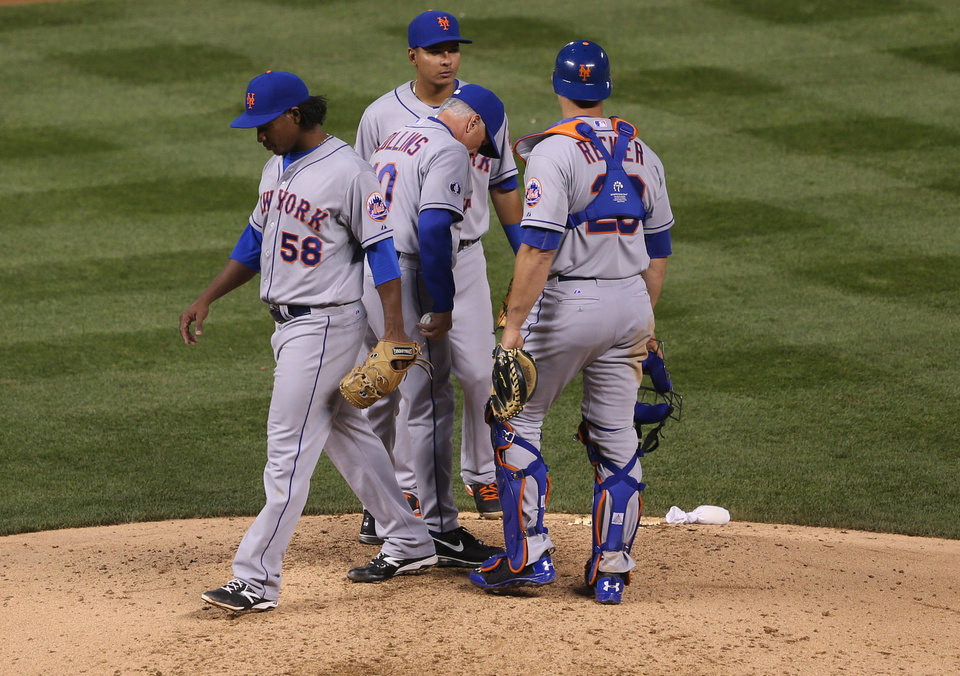 Photo - New York Mets starting pitcher Jenrry Mejia, left, steps off the mound after he was pulled by manager Terry Collins, second from left, as shortstop Ruben Tejada, back, and catcher Anthony Recker look on after he gave up a grand slam to Colorado Rockies' Nolan Arenado in the fifth inning of a baseball game in Denver, Saturday, May 3, 2014. (AP Photo/David Zalubowski)