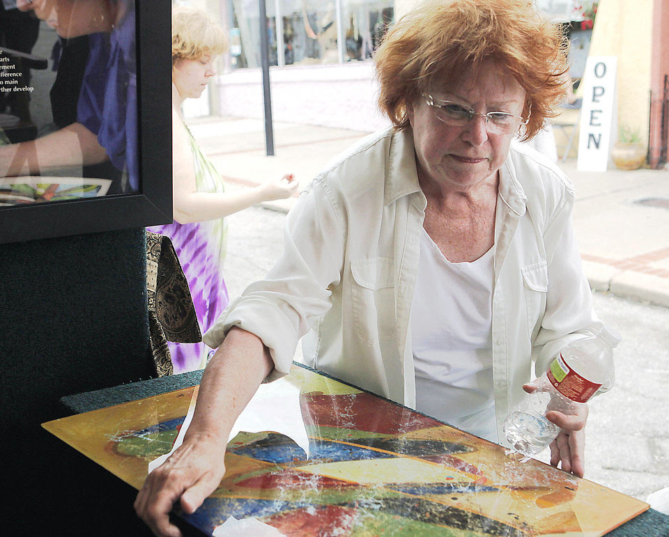 Photo - Jan Brieschke, of Bartlesville, Okla., shows an vividly colored oil painting on glass at the Paseo Arts Festival in Oklahoma City on May 25, 2013. Photo by KT King, The Oklahoman