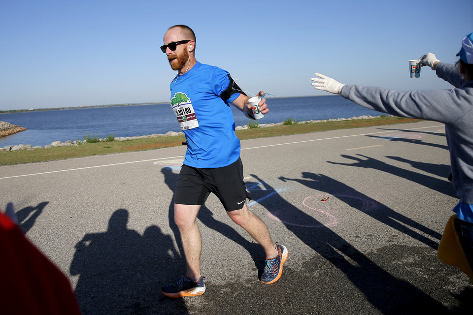 Photo - A relay runner grabs water as he makes his way around Lake Hefner during the Oklahoma City Memorial Marathon in Oklahoma City, Sunday, April 29, 2018. Photo by Bryan Terry, The Oklahoman