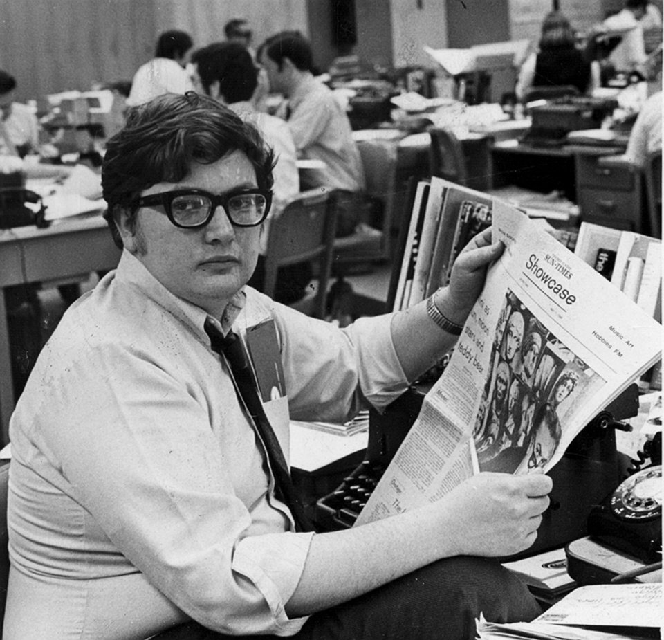 Photo - FILE - This 1969 file photo shows Chicago Sun-Times movie critic Roger Ebert in the newsroom of the paper in Chicago. The Pulitzer Prize-winning critic died Thursday, April 4, 2013. He was 70. Ebert started out as an old-school newspaper man, the kind that has all but vanished: a fierce competitor who spent the day trying to scoop the competition and the night bellied up to the bar swapping stories. Then newspapers fell on hard times, either laying off huge chunks of their staffs or disappearing altogether. But Ebert didn't merely survive. He flourished, largely by embracing television and later the Internet and social networks. (AP Photo/Chicago Sun-Times, Bob Kotalik)
