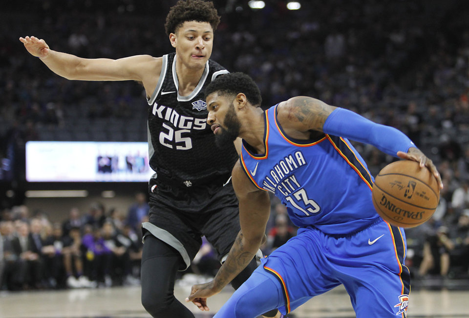 Photo - Oklahoma City Thunder forward Paul George (13) drives to the basket against Sacramento Kings forward Justin Jackson (25) during the first half of an NBA basketball game in Sacramento, Calif., Thursday, Feb. 22, 2018. (AP Photo/Steve Yeater)