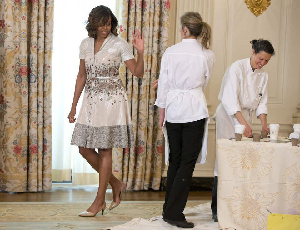 Photo - This photo taken May 12, 2014 shows first lady Michelle Obama waving as she leaves the crafts area as she and Jill Biden hosted their annual Mother's Day tea to honor military mothers at White House in Washington. Sure, living in the White House has its perks. But a clothing allowance is not one of them. First ladies feel all sorts of pressure to project a fashionable look, and over the decades they've tried a range of cash-saving strategies to pull it off without going broke. Even first ladies recycle their clothes, and Michelle Obama recently welcomed military moms to a Mother's Day Tea wearing the same shirtdress she'd worn to lunch with Katy Perry in 2012. (AP Photo)