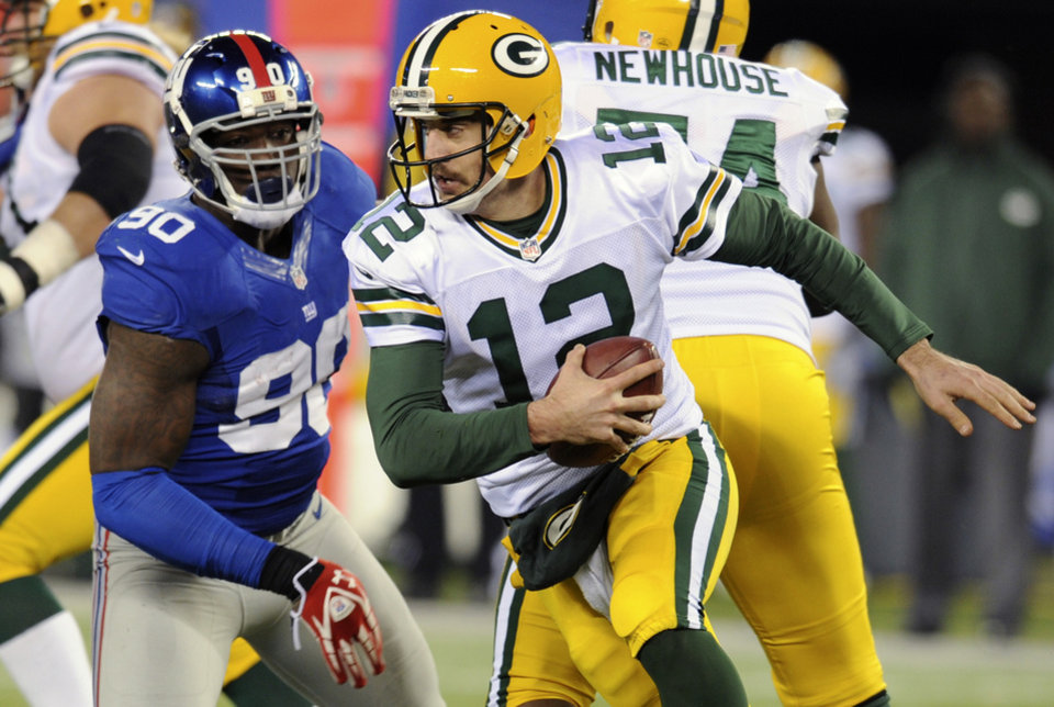 Photo -   Green Bay Packers' Aaron Rodgers (12) scrambles away from New York Giants defensive end Jason Pierre-Paul (90) during the second half of an NFL football game, Sunday, Nov. 25, 2012, in East Rutherford, N.J. (AP Photo/Bill Kostroun)
