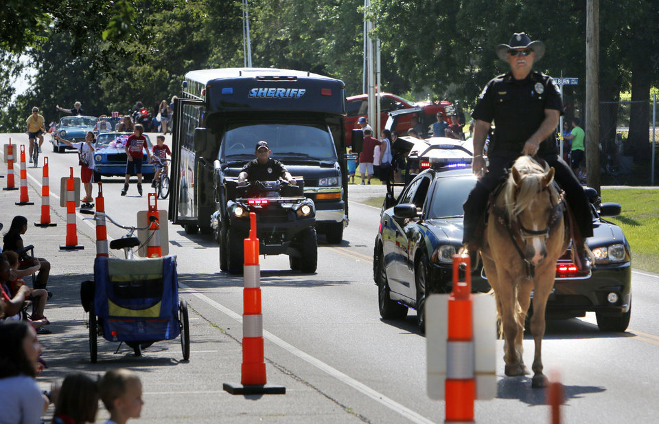 Photo - Members of the Oklahoma County Sheriff's Dept. ride past during Bethany's Fourth of July parade in Bethany, OK, Friday, July 4, 2014,  Photo by Paul Hellstern, The Oklahoman