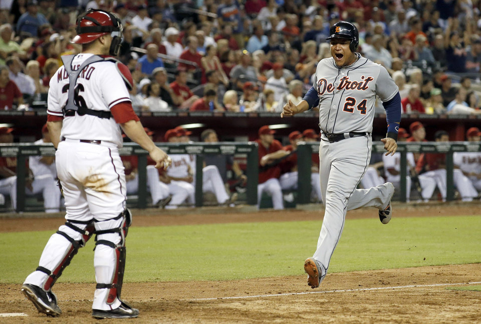 Photo - Detroit Tigers' Miguel Cabrera (24) shouts in celebration as he comes in to score as Arizona Diamondbacks' Miguel Montero, left, looks on during the eighth inning of a baseball game on Tuesday, July 22, 2014, in Phoenix. (AP Photo)