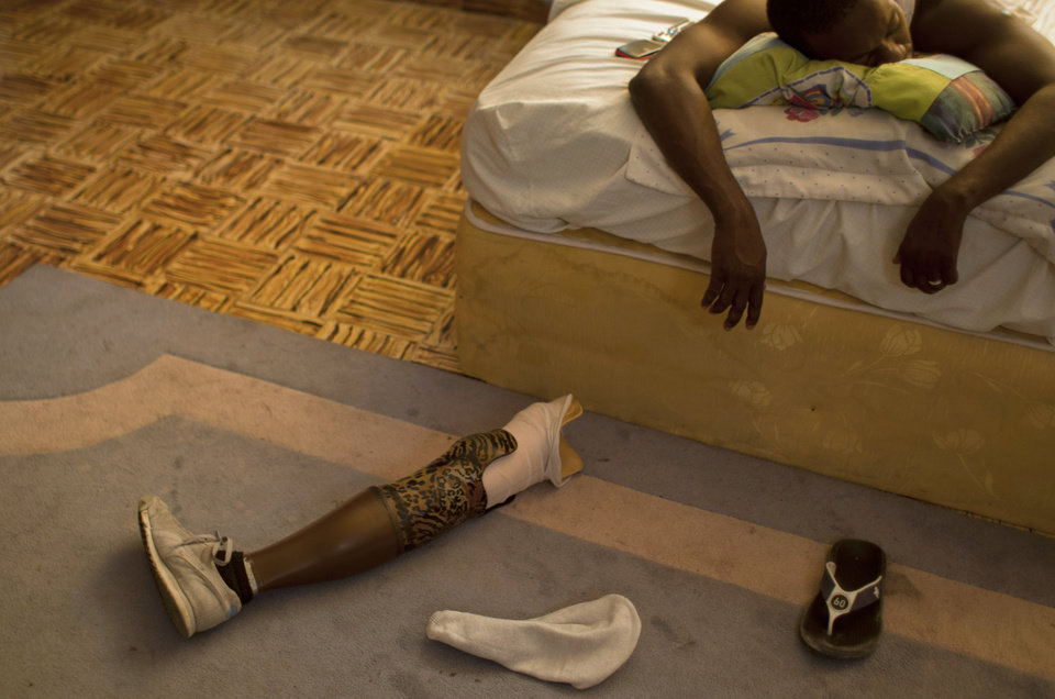 Photo - In this Jan. 17, 2013 photo, professional dancer Georges Exantus sleeps as his prosthetic limb lays on the floor in his bedroom in Port-au-Prince, Haiti.  Exantus thought he'd never dance again. He was lucky just to be alive. The earthquake three years ago in Haiti's capital flattened the apartment where he was living, where he spent three days trapped under a heap of jagged rubble. After friends dug him out, doctors amputated his right leg just below the knee. Exantus says he has learned to ignore the long stares and quiet whispers, products of a longstanding stigma in Haiti for people with disabilities. Before the quake, few resources existed to accommodate Haiti's disabled, and many regard people with disabilities as misfits. (AP Photo/Dieu Nalio Chery)