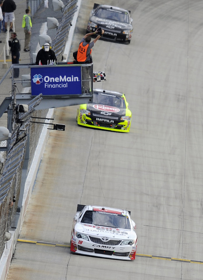 Photo -   Joey Logano (18) takes the checkered flag to win the NASCAR Nationwide Series auto race, Saturday, Sept. 29, 2012, at Dover International Speedway in Dover, Del. Paul Menard finished in second place. (AP Photo/Nick Wass)