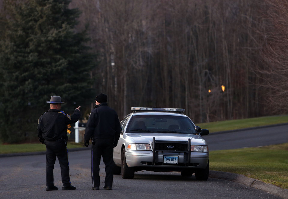 Photo - Police block off a section of Yogananda Street near a house belonging to the mother of a man who opened fire inside a Connecticut elementary school, killing 26 people, including 18 children, Friday, Dec. 14, 2012 in Sandy Hook, Conn.  (AP Photo/Jason DeCrow)