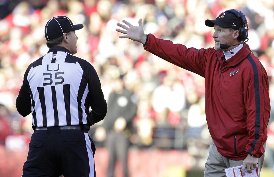 Photo - Arizona Cardinals head coach Ken Whisenhunt, right, talks with line judge John Hussey (35) during the second half of an NFL football game against the San Francisco 49ers in San Francisco, Sunday, Dec. 30, 2012. (AP Photo/Tony Avelar)
