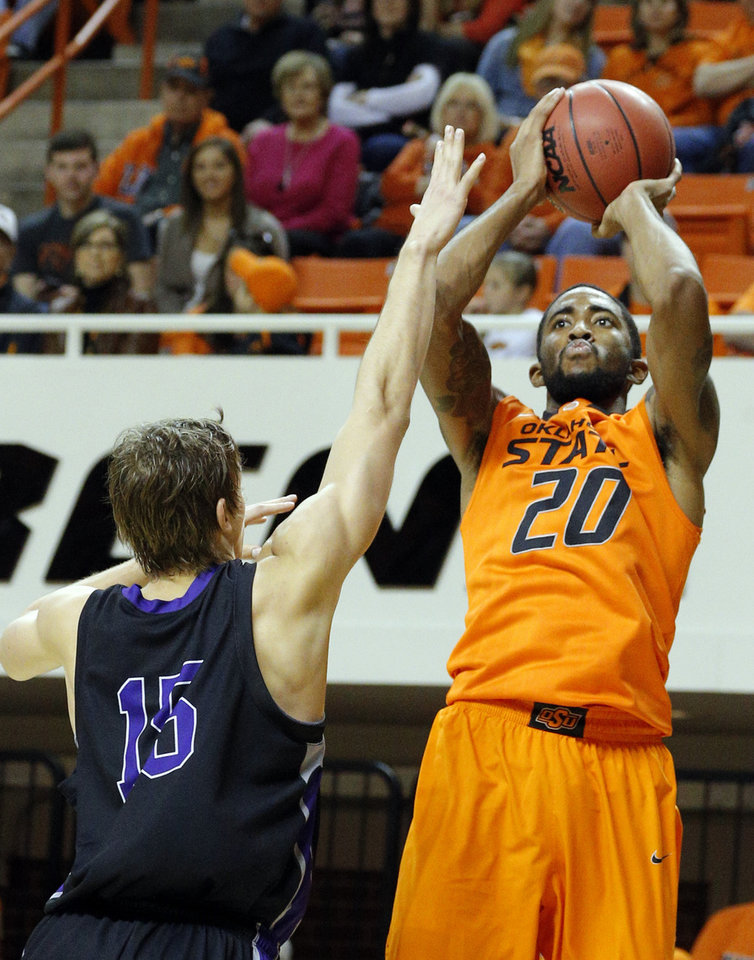 Photo - Oklahoma State's Michael Cobbins (20) shoots over Central Arkansas' Jordan Harks (15) during the men's college basketball game between Oklahoma State University and Central Arkansas at Gallagher-Iba Arena in Stillwater, Okla., Sunday,Dec. 16, 2012. Photo by Sarah Phipps, The Oklahoman